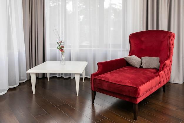 Apartamento de luxo com sofá vermelho de estilo clássico, piso de madeira, mesa de café decorada com vaso de flores e grande janela panorâmica com cortinas transparentes