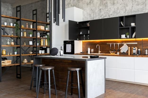 Apartamento de luxo em estilo loft em cores escuras. cozinha moderna com ilha
