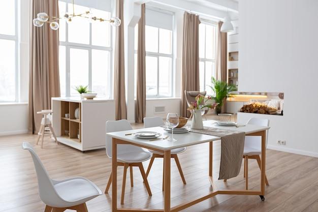 Apartamento espaçoso e luminoso com design de interiores em estilo escandinavo e tons pastel de branco e bege. móveis modernos na área de estar e detalhes modernos na área da cozinha.