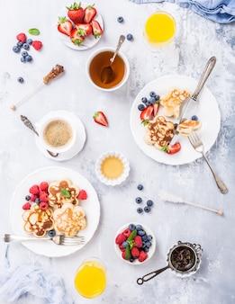 Apartamento leigos com café da manhã com panquecas em forma de flor, bagas e mel na mesa de madeira clara.