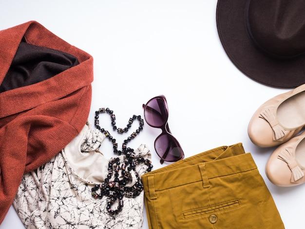 Apartamento leigos com roupas de outono da mulher, chapéu de óculos