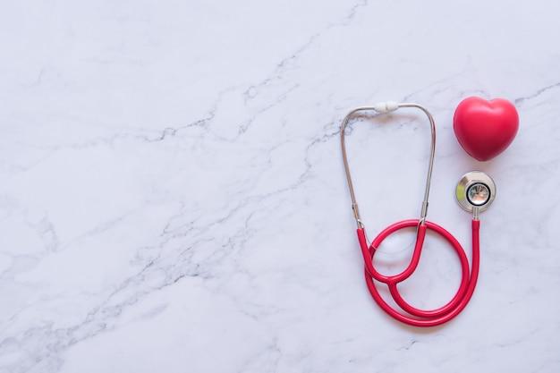 Apartamento leigos de bom conceito saudável, coração vermelho e estetoscópio e mesa no fundo de mármore branco