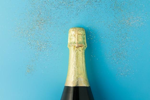 Apartamento leigos de celebração, garrafa de champanhe no fundo azul com glitter.