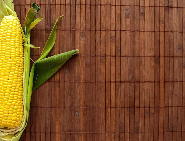 Apartamento leigos de milho amarelo brilhante sobre o fundo de madeira, conceito de estilo de vida saudável, refeição vegetariana