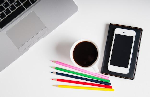 Apartamento leigos no espaço de trabalho de madeira branco com computador portátil, gadget de telefone celular, suprimentos e café preto.