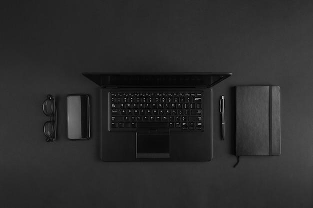 Apartamento mínimo leigos na mesa moderna empresário preto com laptop. conceito criativo de escritório abstrato.