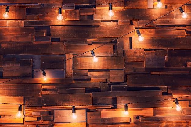Apartamento moderno de design de interiores de estilo clássico escuro com lâmpadas retrô penduradas em um fundo de lâmpadas.