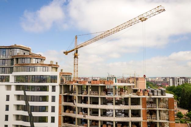 Apartamento ou prédio alto em construção. paredes de tijolo, janelas de vidro, andaimes e pilares de suporte de concreto. guindaste de torre no espaço brilhante da cópia do céu azul.