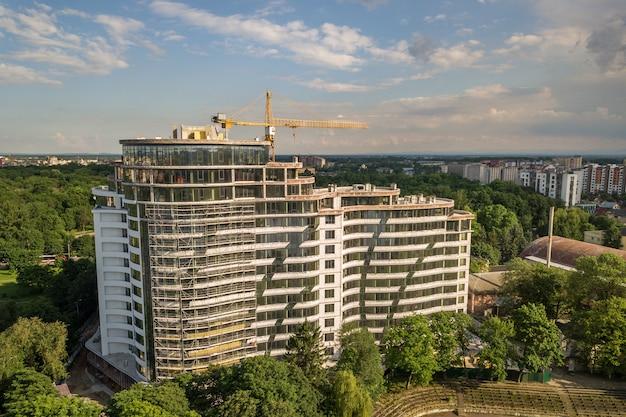 Apartamento ou prédio alto em construção. paredes de tijolo, janelas de vidro, andaimes e pilares de suporte de concreto. guindaste de torre no espaço da cópia do céu azul brilhante