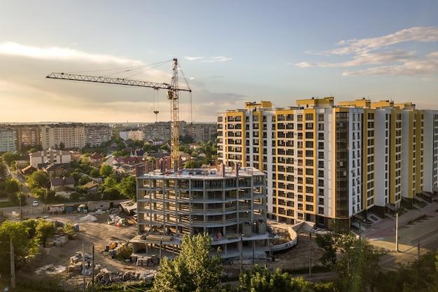 Apartamento ou prédio alto em construção. paredes de tijolo, janelas de vidro, andaimes e pilares de suporte de concreto. guindaste de torre no fundo brilhante do espaço da cópia do céu azul.