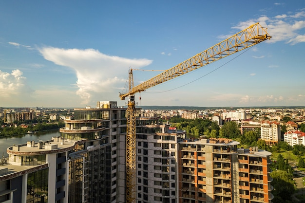 Apartamento ou prédio alto em construção. paredes de tijolo, janelas de vidro, andaimes e pilares de suporte de concreto.