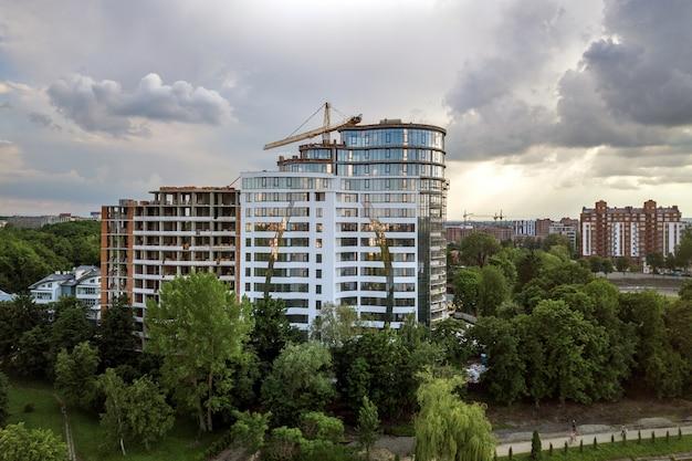 Apartamento ou prédio alto em construção. paredes de tijolos, janelas de vidro, andaimes e pilares de suporte de concreto.