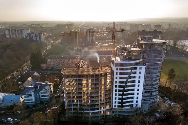 Apartamento ou prédio alto em construção, vista superior. guindaste de torre e paisagem da cidade, estendendo-se para o horizonte. fotografia aérea de zangão.