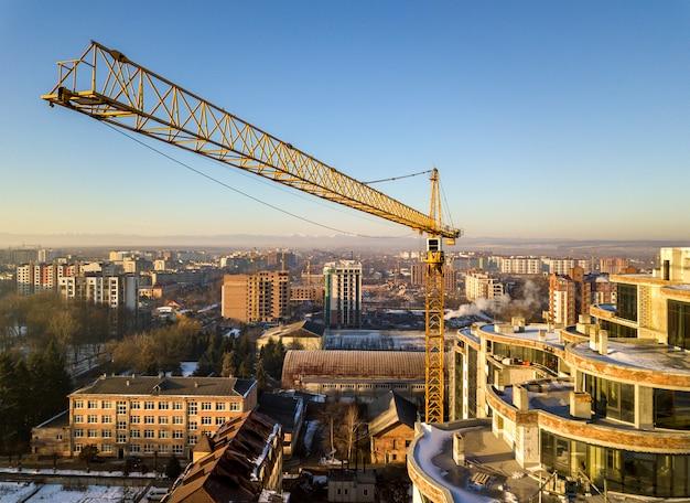 Apartamento ou prédio alto em construção, vista superior. guindaste de torre no espaço brilhante da cópia do céu azul, paisagem da cidade que estica ao horizonte. fotografia aérea de zangão.