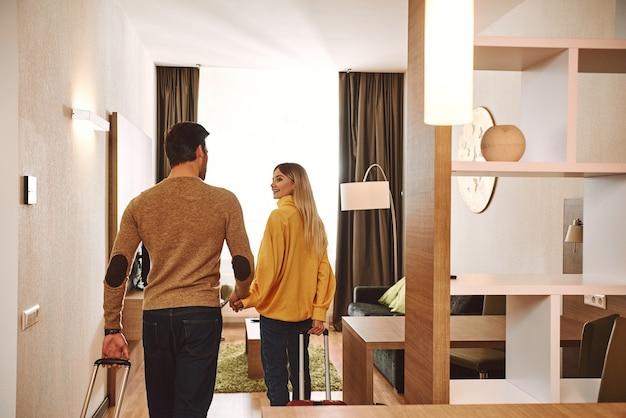 Apartamento temprorário. casal fazendo check-in em seu apartamento alugado para férias, de mãos dadas e felizes por estarem juntos em lua de mel de férias