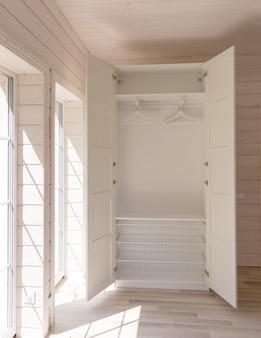 Apartamentos de estilo escandinavo. interior claro do quarto em uma casa de madeira orgânica de cor branca. móveis ikea, guarda-roupa. chão de madeira, paredes, teto de madeira. armário branco. janelas panorâmicas.