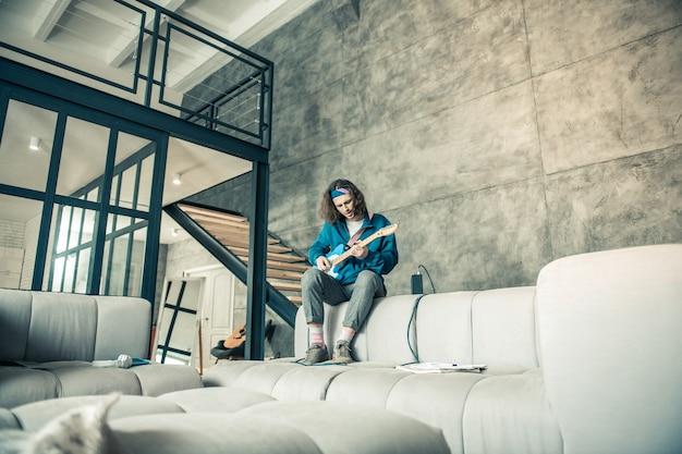 Apartamentos elegantes. homem talentoso contratado há muito tempo sentado no sofá enquanto treina suas habilidades em tocar guitarra profissional
