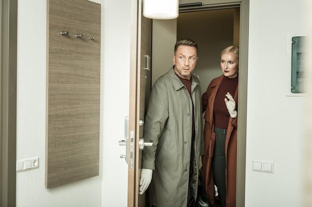 Apartamentos perigosos. dois detetives com aparência profissional usando luvas, inspecionando a sala em busca de ações ilegais