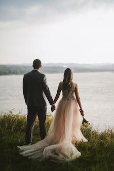 Apenas casal dançando na natureza, de mãos dadas e olhando a bela vista do rio. aproveitando a cada momento em seu dia especial.