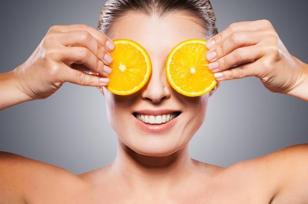 Apenas ingredientes naturais. mulher madura alegre segurando pedaços de laranja na frente dos olhos enquanto fica de pé, isolado no fundo branco