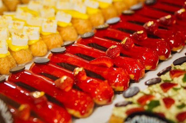 Apenas morangos. saborosos eclairs vermelhos cobertos com geléia e decorados com chocolate e morangos frescos