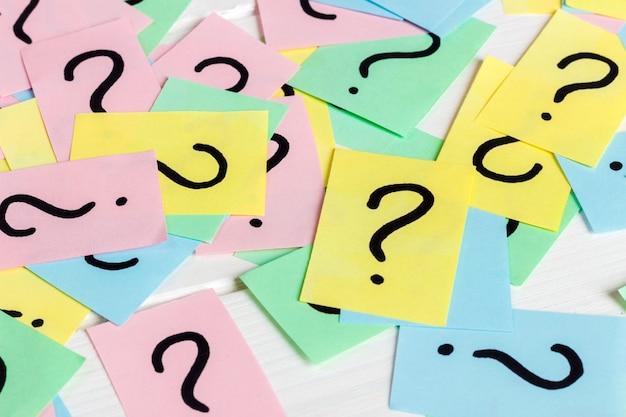 Apenas muitos pontos de interrogação em papéis coloridos