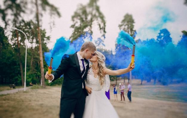 Apenas pares-casado beijando e segurando tochas azuis