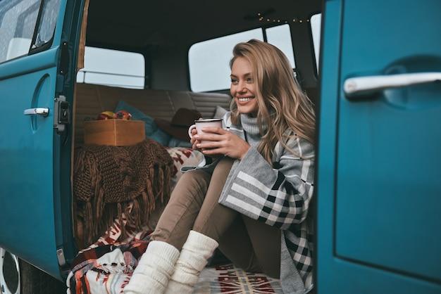 Apenas relaxando. mulher jovem e atraente sorridente segurando uma caneca e desviando o olhar enquanto está sentado dentro da mini van azul estilo retro