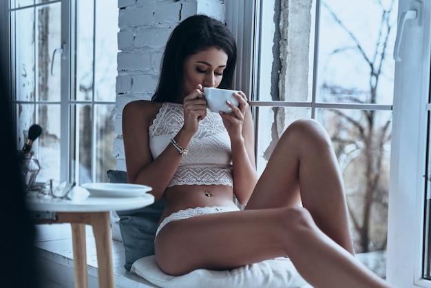 Apenas relaxando. mulher jovem e atraente tomando café da manhã sentado no parapeito da janela em casa