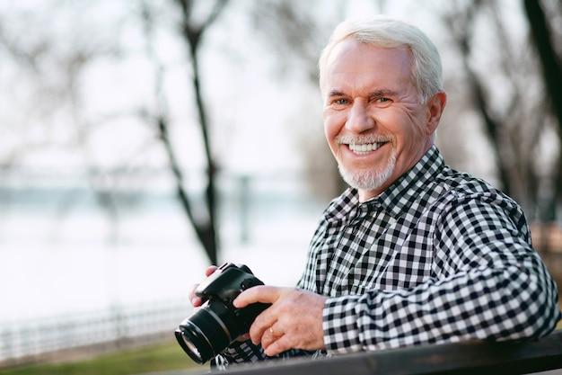 Aperfeiçoe suas habilidades. feliz homem maduro usando a câmera e sorrindo para a câmera