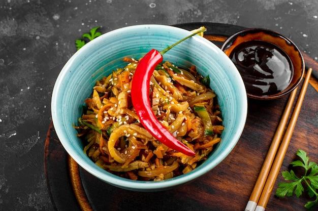 Aperitivo asiático tradicional he ou hwe, salada de lula picante com legumes em uma tigela na placa de madeira