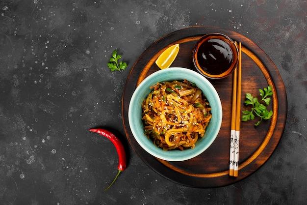 Aperitivo asiático tradicional he ou hwe, salada de lula picante com legumes em uma tigela vista de cima