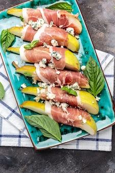 Aperitivo com pêra, queijo azul e presunto prosciutto, delicioso conceito de comida equilibrada, imagem vertical. vista do topo