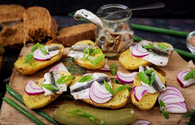 Aperitivo de anchova de arenque e batata assada.