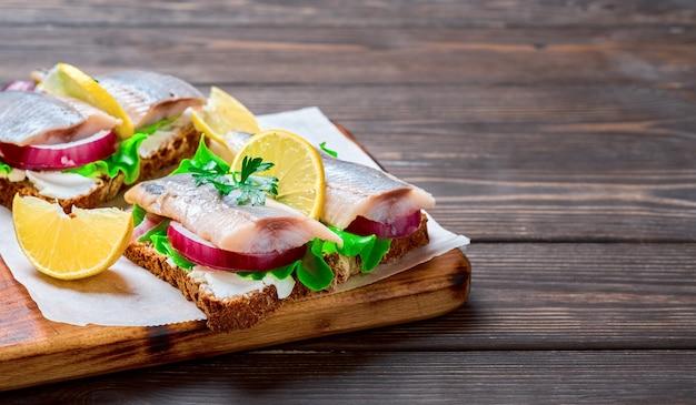 Aperitivo de arenque ou conceito de fast food, sanduíche smorrebrod tradicional. sanduíches de arenque com pão de centeio e cebola, decore com salsa na folha de papel. close-up, mesa de madeira com espaço de cópia