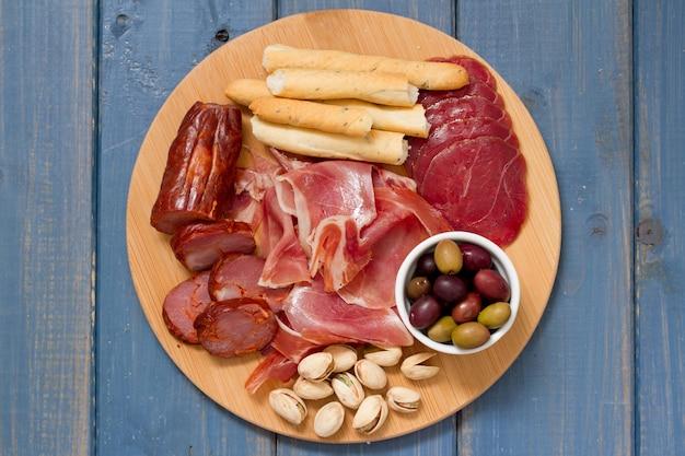 Aperitivo de carne com azeitonas e nozes na bandeja na superfície de madeira azul
