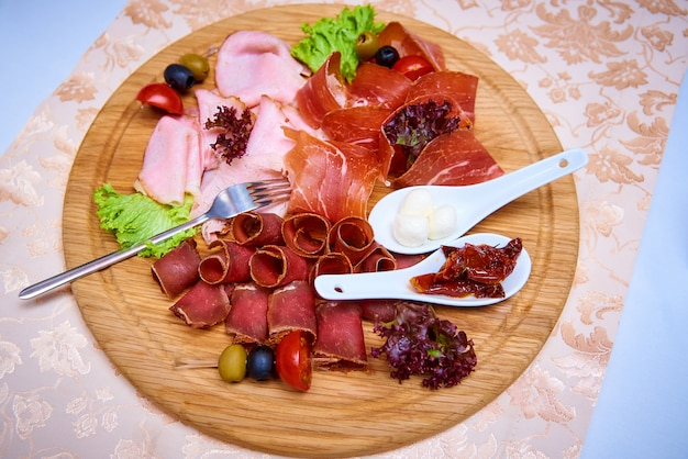 Aperitivo de carne decorado com saladas, azeitonas e tomate