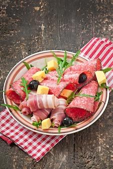 Aperitivo de carne em um prato na superfície de madeira velha
