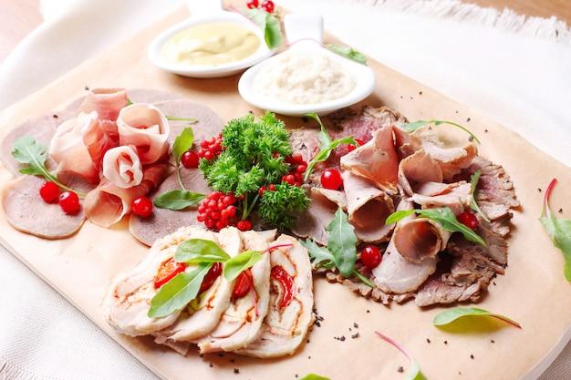 Aperitivo de carne na tábua de madeira: bacon, língua de boi e outros com verduras e molho