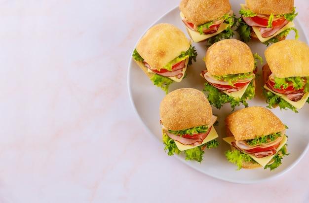 Aperitivo de grãos inteiros pequeno sanduíche roll com presunto e legumes.