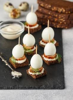 Aperitivo de pão de centeio com ovos de codorna