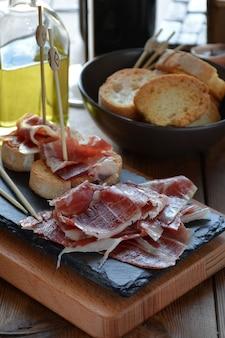 Aperitivo de presunto serrano com pão torrado e acompanhado por um copo de vinho