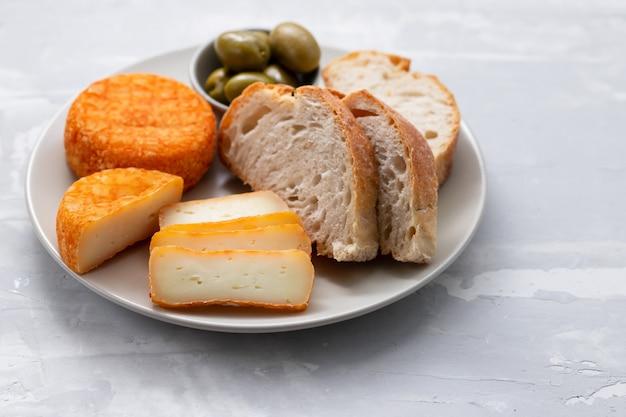 Aperitivo de queijo com pão e azeitonas no prato