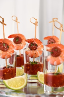 Aperitivo de shish kebab com camarão e chouriço com molho barbecue em copo