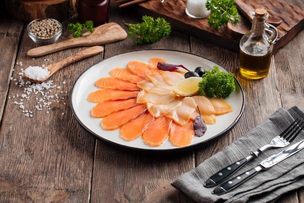 Aperitivo de travessa de peixe defumado na mesa de madeira