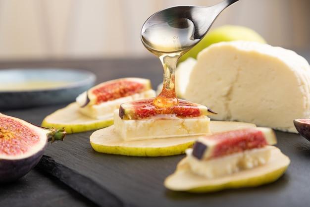 Aperitivo de verão com pêra, queijo cottage, figos e mel na placa de ardósia em um fundo preto de concreto. vista lateral, close-up, foco seletivo.