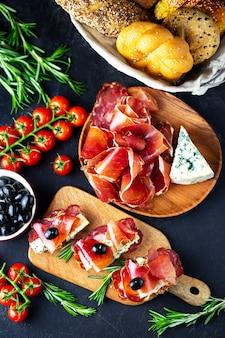 Aperitivo de vinho em uma placa de madeira. queijo vinho branco, jamon, presunto, com salame e azeitonas em um fundo preto. pão fresco com petiscos de queijo e vinho. petiscos saborosos para festas