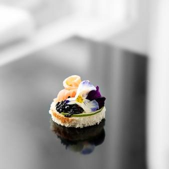 Aperitivo delicioso com peixes e flores comestíveis. conceito de comida, restaurante, menu, catering.