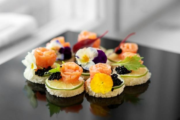 Aperitivo delicioso com salmão e flores comestíveis.