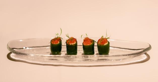 Aperitivo delicioso, pepinos pequenos recheados com queijo light e decorados com caviar de salmão vermelho (foco seletivo)
